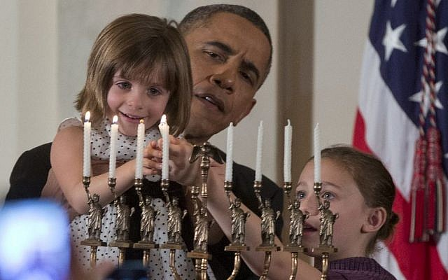 President Barack Obama holds up Kylie Schmitter as she, alongside her sister Lainey Schmitter, lights the menorah during the first of two Hanukkah receptions in the White House, on Thursday, December 5, 2013. (photo credit: AP/Carolyn Kaster)