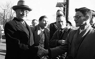 This Nov. 4, 1952 photo shows President Harry Truman smiling as he shakes hands with Associated Press Kansas staffer Harry Rosenthal at trainside in Independence, Mo. as Truman left for Washington after voting. (photo credit: AP Photo/William P. Straeter)