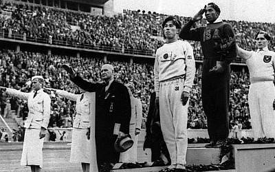 In this August 11, 1936 file photo, Olympic broad jump medalists salute during the medals ceremony at the Summer Olympics in Berlin. From left on podium are: bronze medalist Jajima of Japan, gold medalist Jesse Owens of the United States and silver medalist Lutz Long of Germany. (photo credit: AP Photo/File)