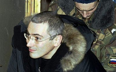 In this Dec. 23, 2003 file photo Mikhail Khodorkovsky, former chief of Russia's largest oil company, Yukos, center, is escorted by police officers as he leaves a court in Moscow, Russia (photo credit: AP/Sergey Ponomarev)
