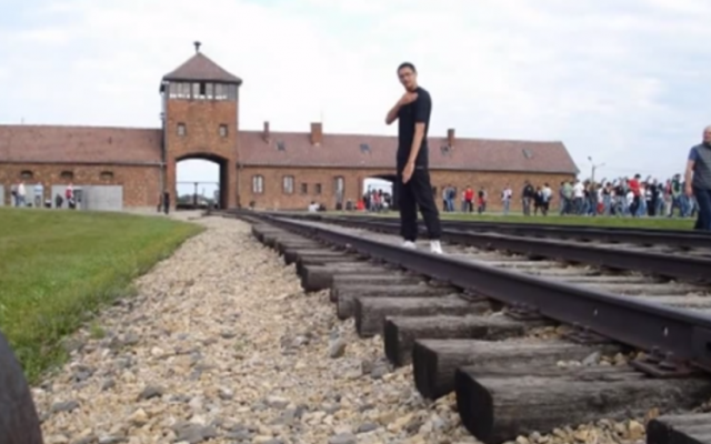 A young man displays the quenelle in front of the main gate of the Auschwitz-Birkenau death camp (photo credit: YouTube screenshot)