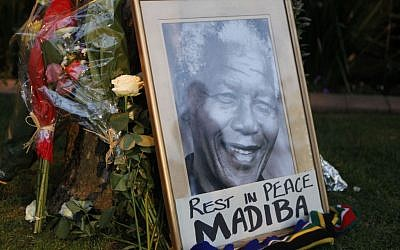 A framed portrait of former president Nelson Mandela and flowers are placed outside Mandela's Johannesburg home Friday, December 6, 2013. (photo credit: AP/Denis Farrell)