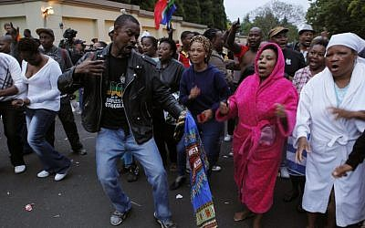 A group of mourners sing and dance outside the Johannesburg home of former president Nelson Mandela on Friday, December 6, 2013. (photo credit: AP/Denis Farrell)