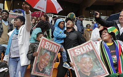 People hold images of former South African president Nelson Mandela ahead of his memorial service at the FNB Stadium in Soweto, near Johannesburg, South Africa, Tuesday Dec. 10, 2013. (Photo credit: AP/Bernat Armangue)