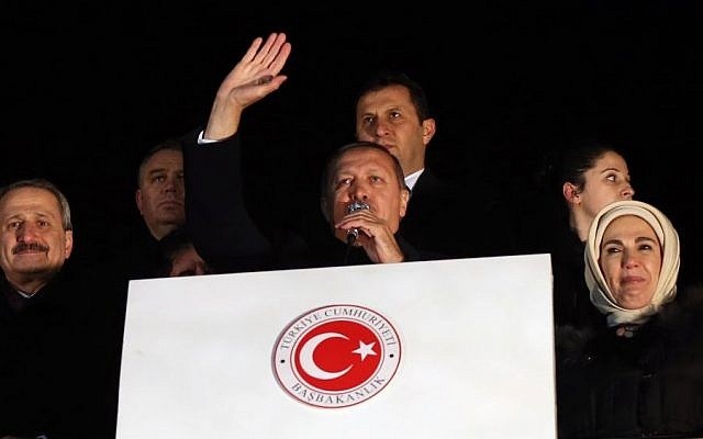 In this photo taken late Tuesday, Dec. 24, 2013, Turkey's Prime Minister Recep Tayyip Erdogan, center, is flanked by his wife Emine Erdogan, right, and Economy Minister Zafer Caglayan, left, as he addresses supporters at the Esenboga Airport, Ankara, Turkey. Interior Minister Muammer Guler and Caglayan resigned from their posts on Wednesday, Dec. 25, 2013, days after their sons were arrested in a massive corruption and bribery scandal that has targeted Erdogan's allies and has become the worst crisis in his decade in power. Caglayan and Guler both stepped down on Wednesday, despite denying any wrongdoing. (Photo credit: AP)