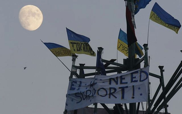 The moon rises over a metal base of destroyed metal Christmas trees decorated with Ukrainian national flags during a pro-European Union rally in Kiev's Independence Square, Saturday, December 14, 2013.(photo credit: AP/Dmitry Lovetsky)