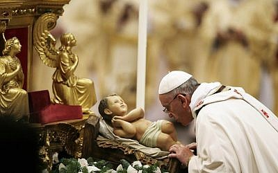 Pope Francis kisses a statue of baby Jesus as he celebrates the Christmas Eve Mass in St. Peter's Basilica at the Vatican, Tuesday, Dec. 24, 2013 (photo credit: AP/Gregorio Borgia)