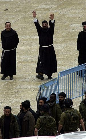A priest reacts as the last group of Palestinians leave Bethlehem's Church of the Nativity May 10, 2002 under a deal intended to end a five-week armed standoff at one of Christianity's holiest shrines (photo credit: Gil Yohanan/Flash90)