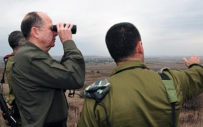 Israeli Defense Minister Moshe Ya'alon using binoculars to cast a glimpse to the Syrian territory from the Golan heights on December 3, 2013 (photo credit: Ariel Hermoni/Ministry of Defense/Flash 90)