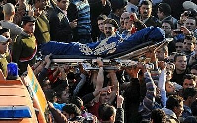 Egyptians carry the coffin of a victim killed in an explosion at a police headquarters, in the Nile Delta city of Mansoura, 110 kilometers (70 miles) north of Cairo, Egypt, Tuesday, Dec. 24, 2013 (photo credit: AP/Ahmed Omar)