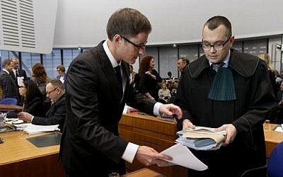 Michael Pietrzak, right, one of the lawyers of Abd al-Rahim al-Nashiri and Abu Zubaydah, is helped by an assistant as he arrives at the forth section of the European Court of Human Rights in Strasbourg, eastern France, Tuesday, Dec. 3, 2013 (photo credit: AP Photo/Christian Lutz)