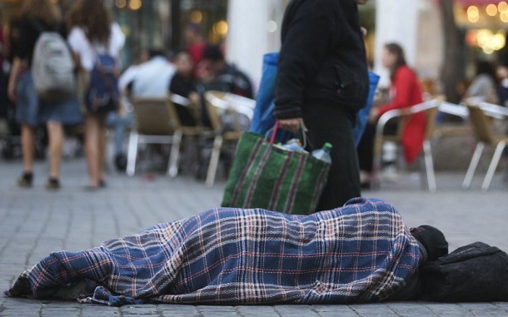 People walk by a homeless man sleeping on the street, in the center of Jerusalem, on November 10, 2013. (photo credit: Nati Shohat/Flash90)