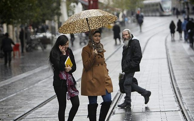 A woman holds an umbrella to protect herself from the rain as she crosses Jerusalem's Jaffa Road, Tuesday, December 10, 2013 (photo credit: Miriam Alster/Flash90)