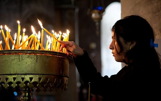 A girl lights candles in Bethlehem's Church of the Nativity (Nativity candles photo via Shutterstock)