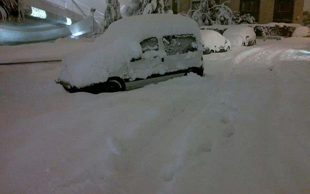 A car covered in snow at the entrance to Jerusalem Friday morning. (photo credit: Israel Hatzolah)