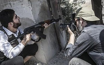 Spanish photographer Ricardo Garcia-Vilanova, right, who was kidnapped in Syria 11 weeks ago takes photographs of a Free Syrian Army fighter in Aleppo, Syria. (AP Photo/Narciso Contreras)