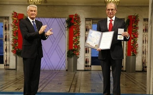 Ahmet Uzumcu, right, Director General of the Organization for the Prohibition of Chemical Weapons receives the Nobel Peace Prize from Chairman of the Norwegian Nobel Committee Thorbjorn Jagland in City Hall Oslo Tuesday Dec. 10, 2013 (photo credit: AP/Cornelius Poppe / NTB scanpix)