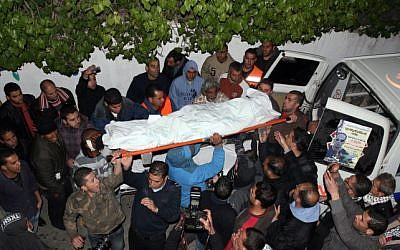 Palestinian men stand next to the body of Mustafa Tamimi on its way to a hospital morgue in the West Bank city of Ramallah, on December 10, 2011. (photo credit: Issam Al Rimawi/Flash90)