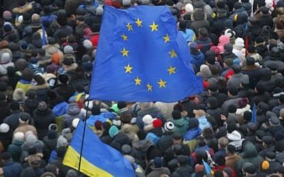 European Union and Ukrainian national flags fly above a crowd of Pro-European Union activists gathered during a rally in Independence Square in Kiev, Ukraine, Sunday, Dec. 8, 2013 (photo credit: AP/Sergei Grits)