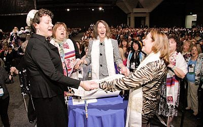 A group of women hold hands around the Torah during the Shabbat morning service at the Union for Reform Judaism's biennial conference in San Diego, December 14, 2013. (URJ via JTA)