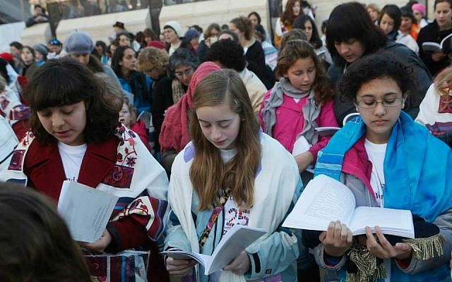 Eliza Moss-Horwitz, Lucy Sattler and Alexandra Schwartz pray with Women of the Wall. Schwartz (right) holds an empty Torah cover beneath her prayer book, symbolizing the Torah scroll the group was prevented from bringing in to the Kotel plaza, January 2014. (photo credit: Courtesy of Moving Traditions)