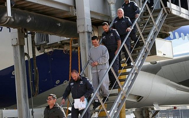 A handcuffed Yitzhak Abergil is led off a plane from the US by police and prison service officials (Photo credit: Israel Prison Service)