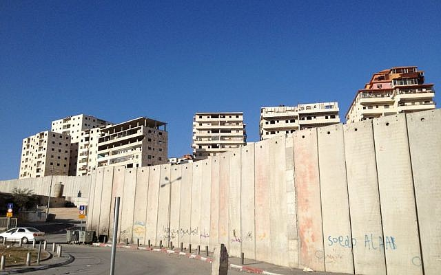 Apartment buildings in Ras Khamis peek over the security barrier in East Jerusalem (photo credit: Elhanan Miller/Times of Israel)