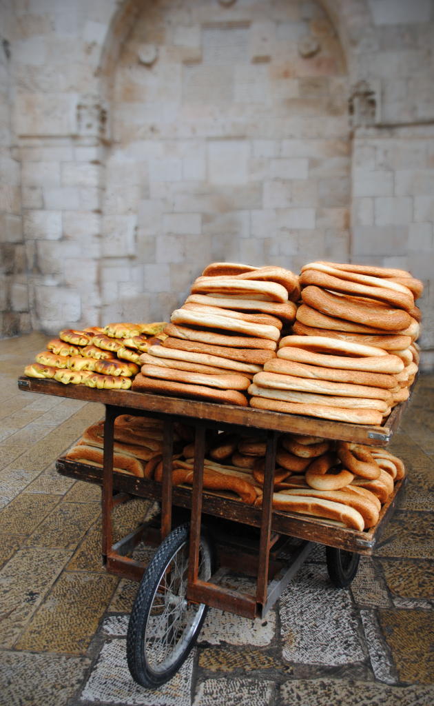 "Michelle Abramson took this untitled photo taken in the Old City of Jerusalem: ""This photo was taken right at the entrance of the old city of Jerusalem. As you walk through the gate and enter the cobbled streets, a street vendor sits there with a cart of this long shaped bread piled high."" (photo credit: Michelle Abramson)"