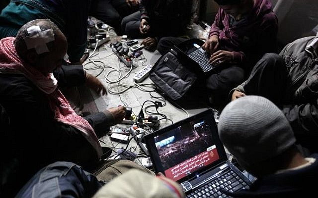Egyptian anti-government bloggers work on their laptops from Cairo's Tahrir Square, on February 10, 2011 (photo credit: Patrick Baz/AFP)