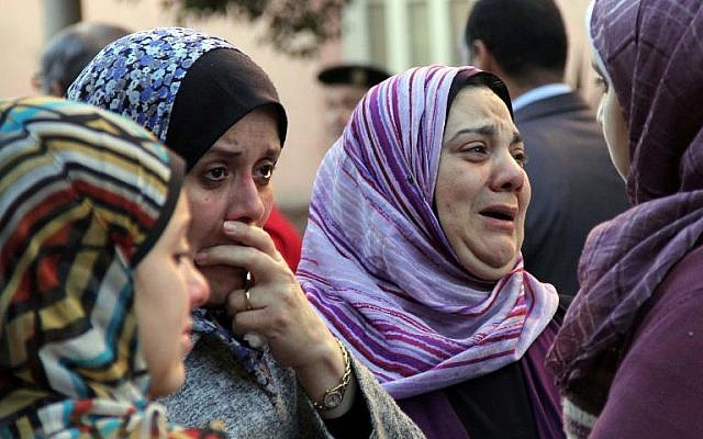 Egyptian relatives mourn during the funeral of General Mohamed Saeed in Cairo, on January 28, 2014. (photo credit: AFP /Ahmed Tarana)