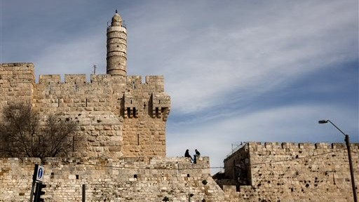 In this March 7, 2012 file photo, a couple sits next to the Tower of David on the wall surrounding Jerusalem's Old City. (photo credit: AP/Sebastian Scheiner)