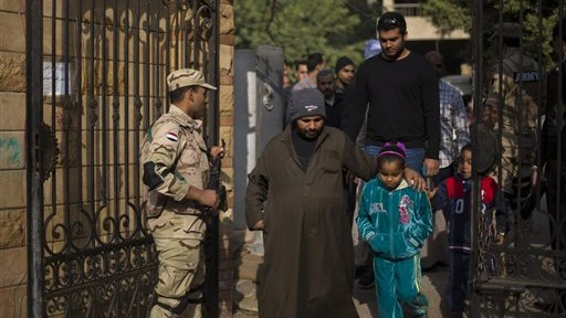 Egyptians walk into a polling center to vote in the country's constitutional referendum, in Cairo, Egypt, Wednesday, January 15, 2014 (photo credit: AP/Khalil Hamra)