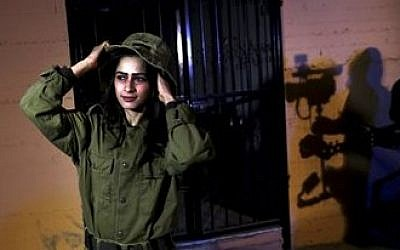 Fayka al-Najar, who plays an Israeli female soldier, adjusts her hat on the set of 'Losing Shalit,' Jan. 29, 2014 (photo credit: Hatem Moussa/AP)