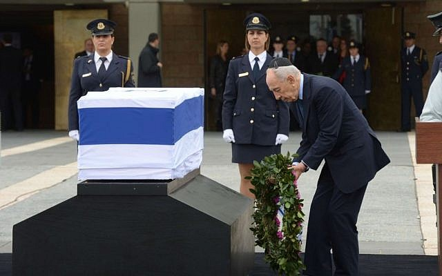 President Shimon Peres lays a wreath next to the casket of former prime minister Ariel Sharon, Sunday, January 12, 2014 (photo credit: Amos Ben Gershom/GPO)