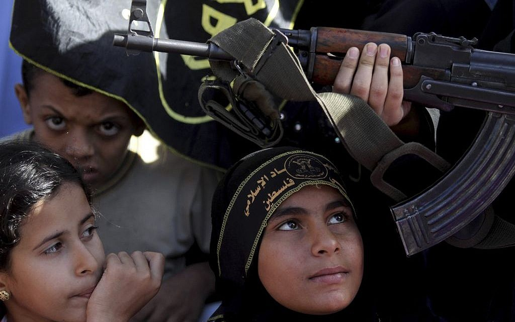 Palestinian children sit next to a woman holding a gun during an Islamic Jihad rally in Gaza City (photo credit: AP/Hatem Moussa)