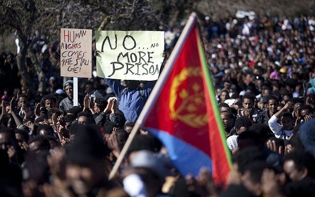 African migrants hold posters and one holds an Eritrean flag during a protest outside the Knesset in Jerusalem, January 8, 2014. (AP Photo/Ariel Schalit)