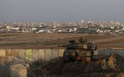 Illustrative. An Israeli tank parks in position overlooking the Gaza Strip on December 25, 2013. (AP/Tsafrir Abayov)