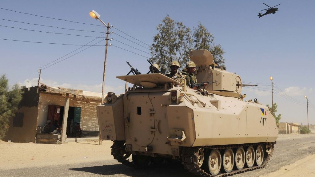 Egyptian Army soldiers patrol in an armored vehicle backed by a helicopter gunship during a sweep through villages in in Sheikh Zuweyid, northern Sinai, Egypt, May 12, 2013 (photo credit: AP)