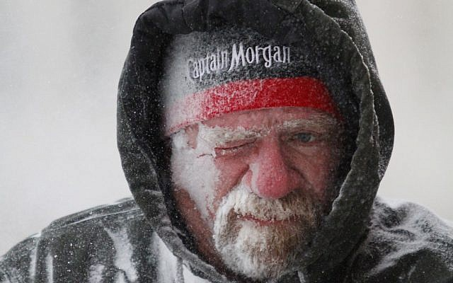 Allan Umscheid, owner of Yards By Al in Lawrence, Kansas, feels the bitter wind and catches drifting snow on his face as he runs a snow blower early Sunday morning, January 5, 2014 (photo credit: AP/The Journal-World, Mike Yoder)