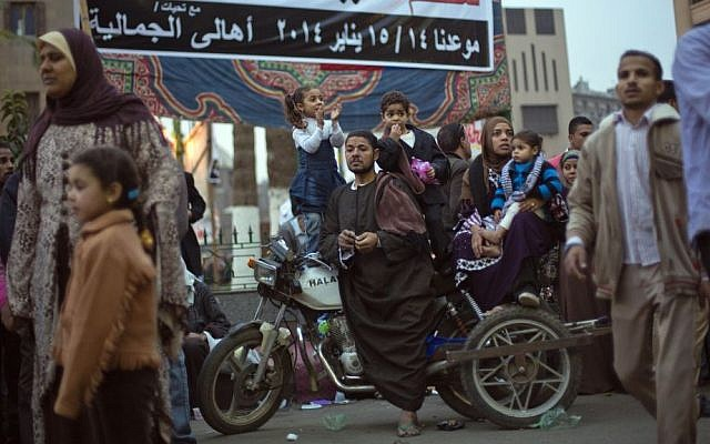 "An Egyptian family sit on a motorbike under a banner with Arabic writing that reads,""Go down, participate and say yes for Egypt's constitution and no for terrorism,"" as they watch a march to mark the birthday of the Prophet Muhammad in Cairo, Egypt, Monday, January 13, 2014. (photo credit: AP Photo/Khalil Hamra)"