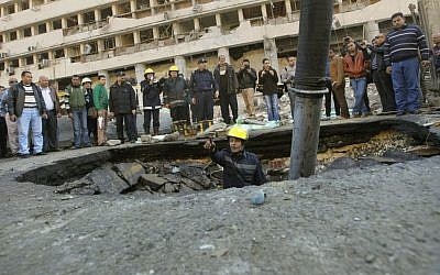 An Egyptian firefighter checks a crater made by a blast at the Egyptian police headquarters in downtown Cairo, Egypt, Friday, Jan. 24, 2014 (photo credit: AP/Amr Nabil)