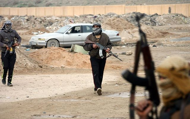 Gunmen patrol after clashes with Iraqi security forces in Fallujah, 40 miles (65 kilometers) west of Baghdad, Iraq, Sunday, Jan. 5, 2014. (photo credit: AP)