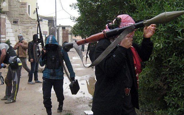 Amid clashes with Iraqi security officials, unidentified gunmen patrol in Fallujah, 40 miles (65 kilometers) west of Baghdad, Iraq, Saturday, Jan. 11, 2014.  (photo credit: AP)