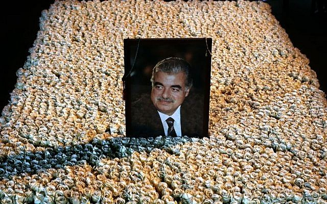 A portrait of slain Lebanese prime minister Rafik Hariri sits on his grave, which is covered by flowers in downtown Beirut, Lebanon, on Wednesday, January 15, 2014 (photo credit: AP/Hussein Malla)