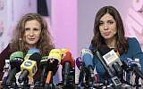 Russian punk band Pussy Riot members Nadezhda Tolokonnikova, right, and Maria Alekhina smile during their news conference in Moscow, Russia, on Friday, Dec. 27, 2013. Tolokonnikova and Alekhina were granted amnesty on Monday, Dec. 23, two months short of their scheduled release after spending nearly two years in prison for their protest at Moscow's main cathedral. (AP Photo/Ivan Sekretarev)