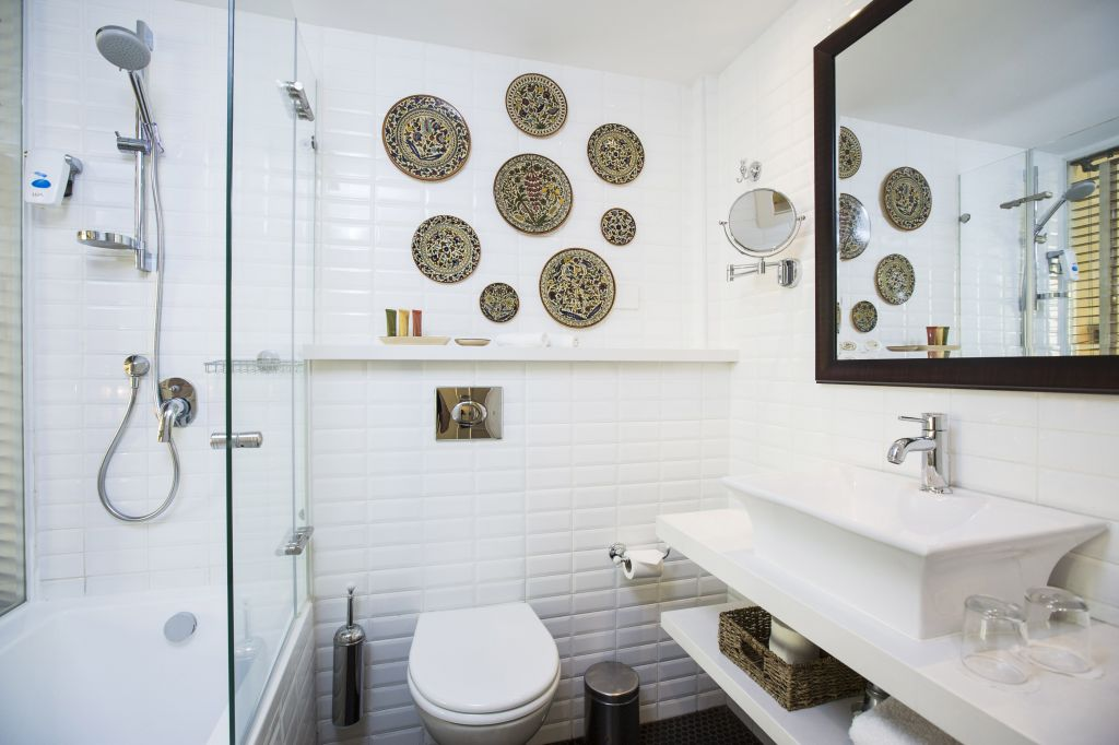 No bathtubs, but wide showers and an Armenian plate collection in each white-tiled bathroom (Courtesy Arthur Hotel)