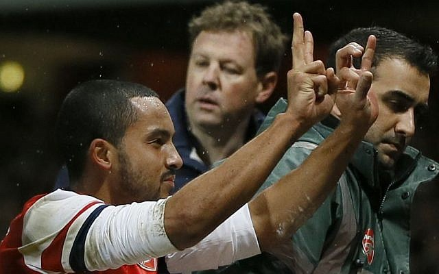 Arsenal's Theo Walcott gestures to the crowd to show the score of 2-0, as he is stretchered off in front of Tottenham fans during the English FA Cup third round soccer match between Arsenal and Tottenham Hotspur at the Emirates Stadium in London, Saturday, Jan. 4, 2014. Arsenal won the match 2-0. (photo credit: AP Photo/Kirsty Wigglesworth)