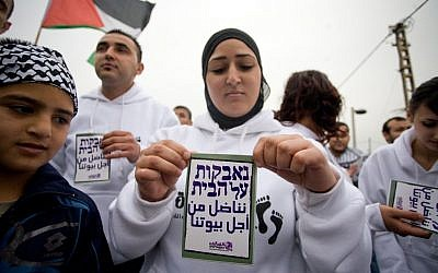 A Palestinian woman holds up a sign reading 'fighting for our homes' during a Land Day demonstration in Jaffa, April 2, 2011 (photo credit: Dima Vazinovich/Flash90)