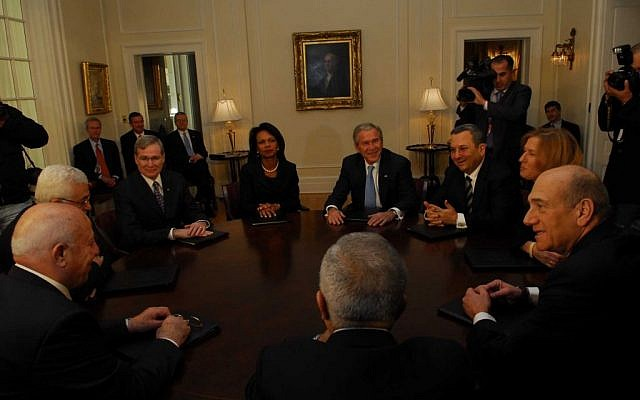 Palestinian Authority President Mahmoud Abbas (L) speaking with his chief negotiator, former Palestinian prime minister Ahmed Queria, in a round table meeting in Annapolis in November 2007 with US president George Bush and US secretary of state Condoleezza Rice, and the Israeli side led by prime minister Ehud Olmert (2,R), foreign minister Tzipi Livni and defense minister Ehud Barak. At right is Palestinian prime minister Salam Fayyad. (Photo credit: Avi Ohayon, GPO/Flash90)