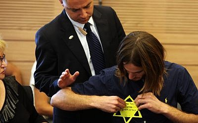 Meir Schijveschuurder, who lost his parents and three of his brothers in the suicide bombing at the Sbarro pizza parlor in Jerusalem in 2001, puts on a yellow Star of David that says 'Modern Holocaust survivor in the Jewish state' at a session of the Labor, Welfare and Health Committee at the Knesset in Jerusalem, on July 11, 2011, during a committee session regarding the Terror Victims Stipends Bill. (photo credit: Kobi Gideon/Flash90)